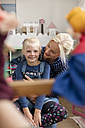 Happy little girl watching Punch and Judy show together with her mother in children's room - MIDF00803
