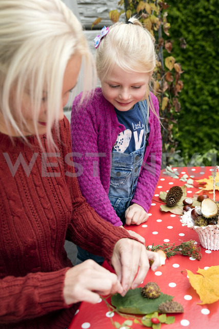 Little girl watching her mother tinkering autumnal decoration - MIDF00806