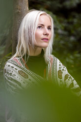 Portrait of blond woman with shawl leaning against tree trunk - MIDF00812