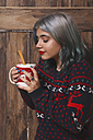 Young woman enjoying a hot chocolate in front of wooden wall - RTBF00465