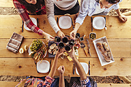 Friends clinking glasses at outdoor table with red wine and cold snack - ZEDF00381