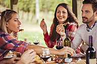 Friends socializing at outdoor table with red wine and cold snack - ZEDF00384