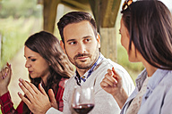 Friends socializing outdoors with red wine - ZEDF00387