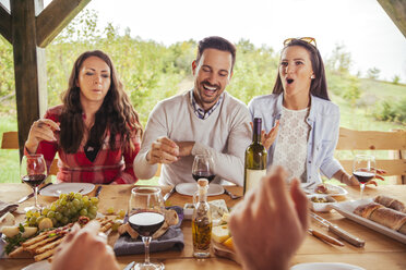 Friends socializing at outdoor table with red wine and cold snack - ZEDF00390