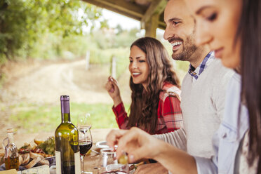 Friends socializing at outdoor table with red wine and cold snack - ZEDF00396