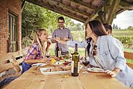 Friends socializing at outdoor table with red wine and cold snack - ZEDF00402