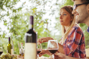 Couple having red wine at outdoor table - ZEDF00405