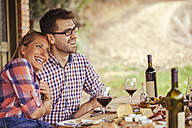 Happy couple at outdoor table with red wine and cold snack - ZEDF00408