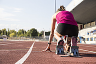 Female runner on tartan track in starting position - ABZF01375
