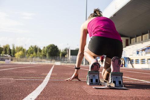 Female runner on tartan track in starting position - ABZF01375
