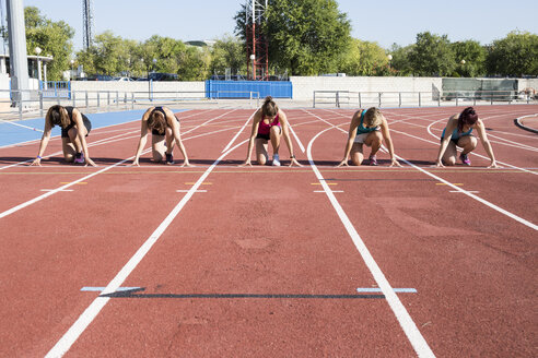 Female runners on tartan track in starting position - ABZF01378