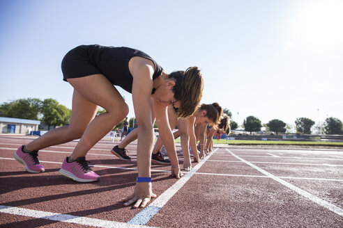 Female runners on tartan track in starting position - ABZF01381