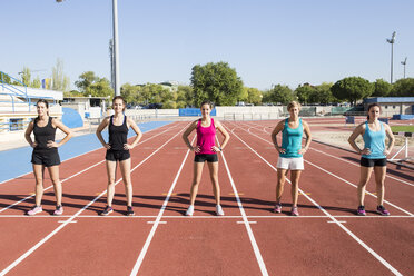 Female runners standing on tartan track at starting line - ABZF01384
