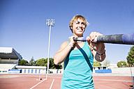 Smiling female pole vaulter preparing - ABZF01390