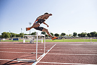 Athlete clearing hurdle during a race - ABZF01402