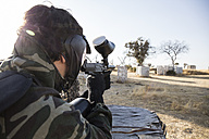 Paintball player aiming with paintball gun during a paintball game - ABZF01420