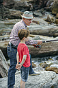 Grandfather and grandson fishing together at rock coast - DAPF00415