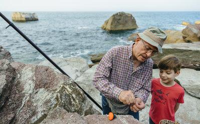 Grandfather teaching grandson fishing at the sea - DAPF00421