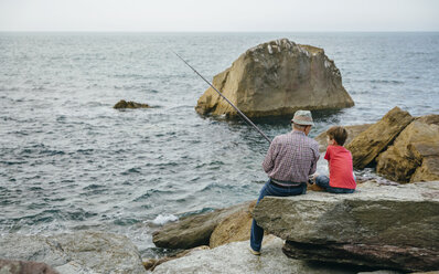 Grandfather and grandson fishing together at the sea sitting on rock - DAPF00424