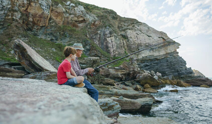 Grandfather and grandson fishing together at the sea sitting on rock - DAPF00427
