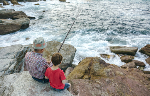 Grandfather and grandson fishing together at the sea sitting on rock - DAPF00430