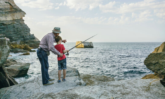 Grandfather and grandson fishing together at the sea - DAPF00433