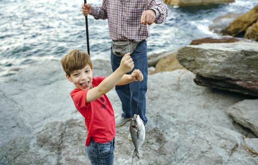 Happy boy holding fish on fishing line caught by his grandfather - DAPF00439