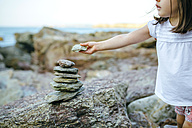 Girl stacking stones at rocky coast - DAPF00448