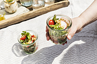 Person holding jar with vegetarian oat salad - EVGF03110