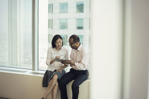 Business people with digital tablet sitting on window sill, discussing - WESTF21760
