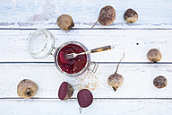 Preserving jar of pickled beetroots and whole and sliced beetroots on wood - LVF05505