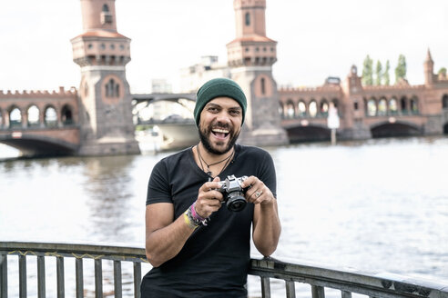 Germany, Berlin, portrait of happy man with camera standing in front of Oberbaum Bridge - TAMF00703