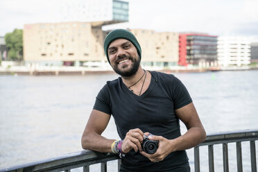 Germany, Berlin, portrait of happy man with camera - TAMF00706
