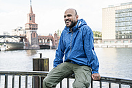 Germany, Berlin, laughing man wearing blue rainjacket sitting on railing in front of Oberbaum Bridge - TAMF00709