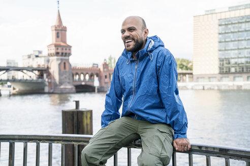 Germany, Berlin, laughing man wearing blue rainjacket sitting on railing in front of Oberbaum Bridge - TAMF00709