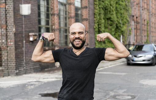 Portrait of smiling man flexing muscles - TAMF00718