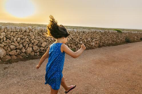 Little girl hopping on street at sunset - MGOF02564