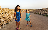 Two laughing little sisters standing on empty road at sunset - MGOF02567