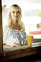 Portrait of blond woman with beverage standing at beach hut - GDF01164