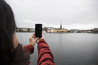 Sweden, Stockholm, back view of woman taking picture with smartphone from the city - ABZF01437