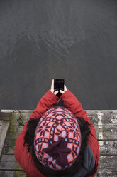Top view of woman sitting on pier text messaging - ABZF01443