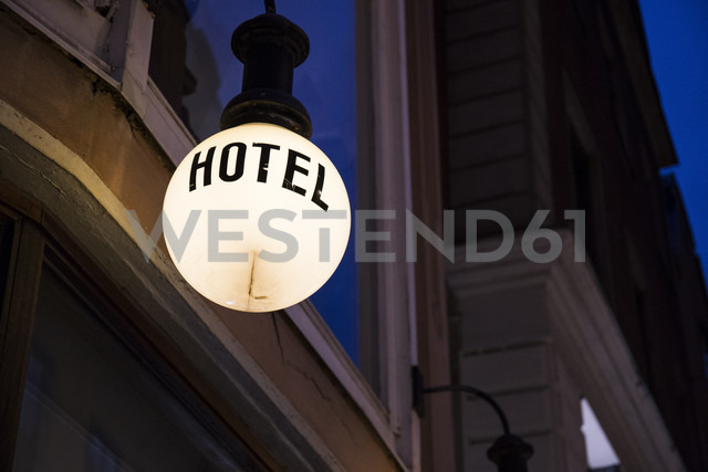 Lighted lamp with the word 'hotel' in front of facade by night - ABZF01446