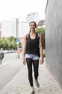 Smiling young woman walking on pavement - TAMF00724