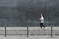 Young woman running in the city - TAMF00739