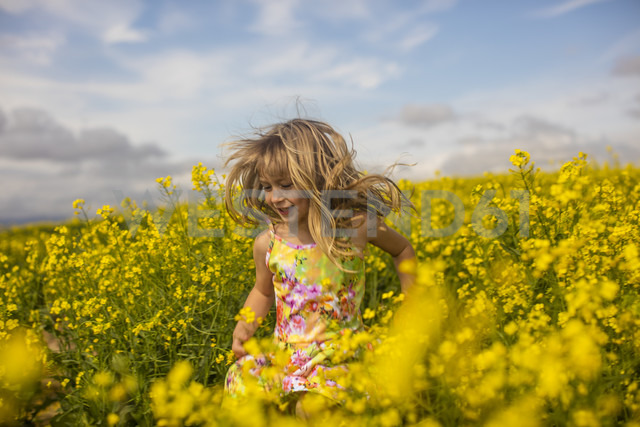 Blond little girl running in rape field - ZEF11132
