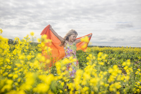 Little girl with orange cloth standing in rape field - ZEF11135