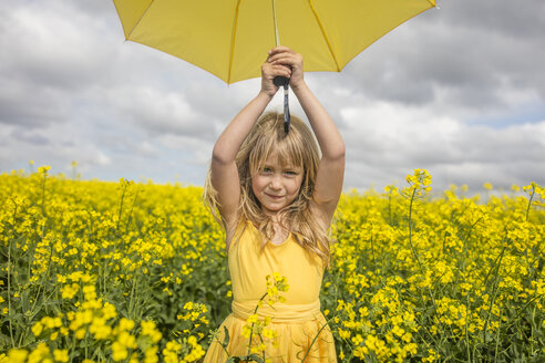 Portrait of blond little girl with yellow umbrella wearing yellow dress standing in rape field - ZEF11138