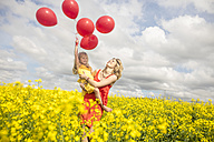 Mother and little daughter having fun with red balloons in rape field - ZEF11141