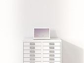 Laptop on old-fashioned filing cabinet, 3d rendering - UWF01051
