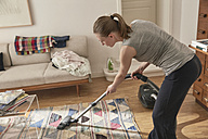 Woman vacuum cleaning at home - SUF00098